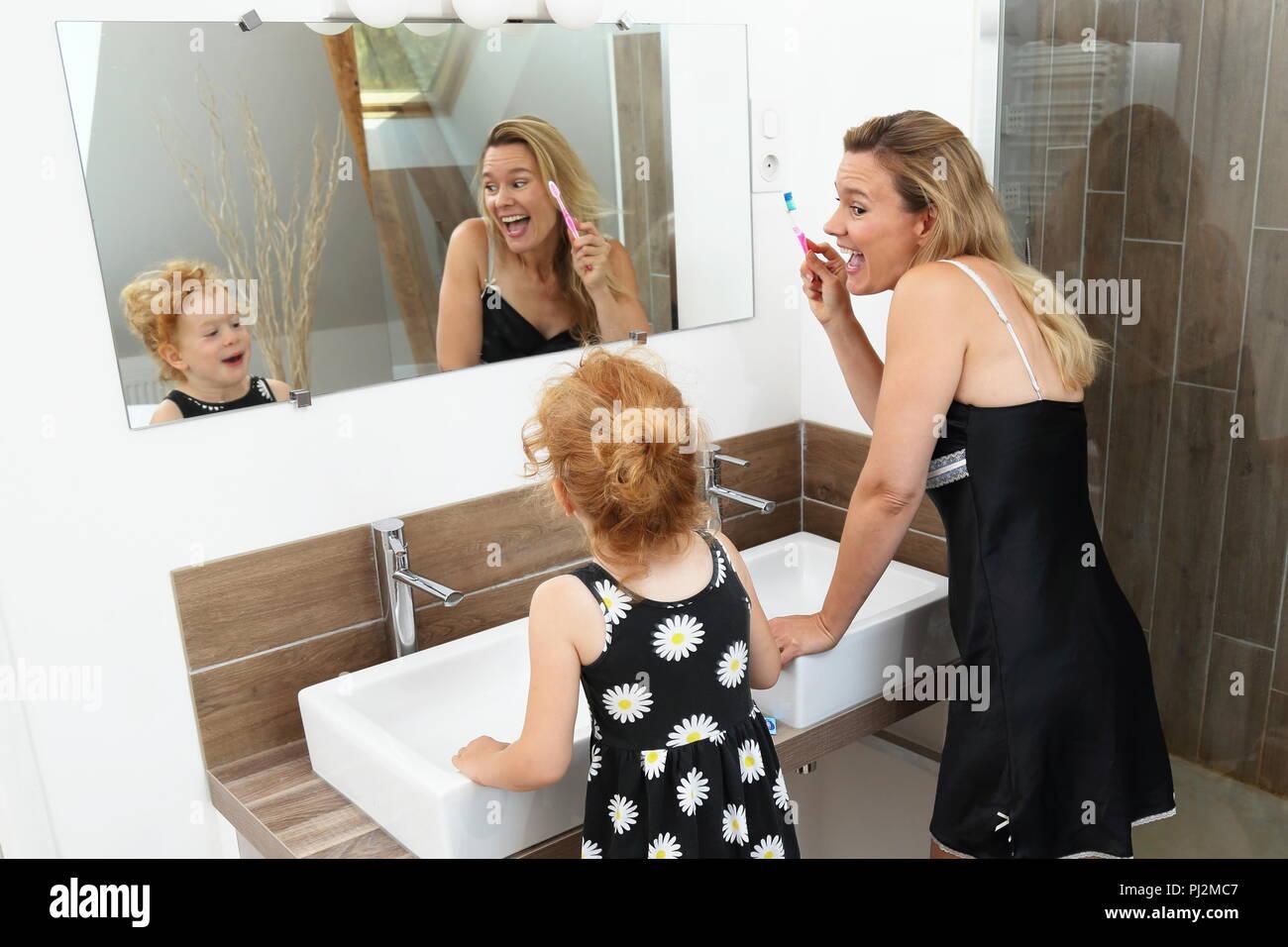 Madre e figlia divertirsi durante lo spazzolamento dei denti in una moderna stanza da bagno Immagini Stock