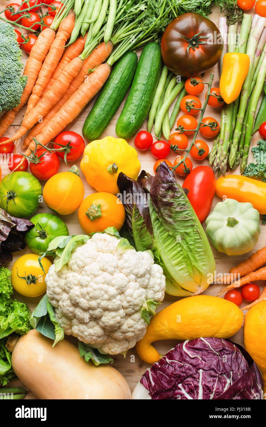 Assortimento di coloratissimi fresche verdure organiche su legno tabella di pino, cibo crudo sfondo, vista dall'alto, verticale, il fuoco selettivo Immagini Stock
