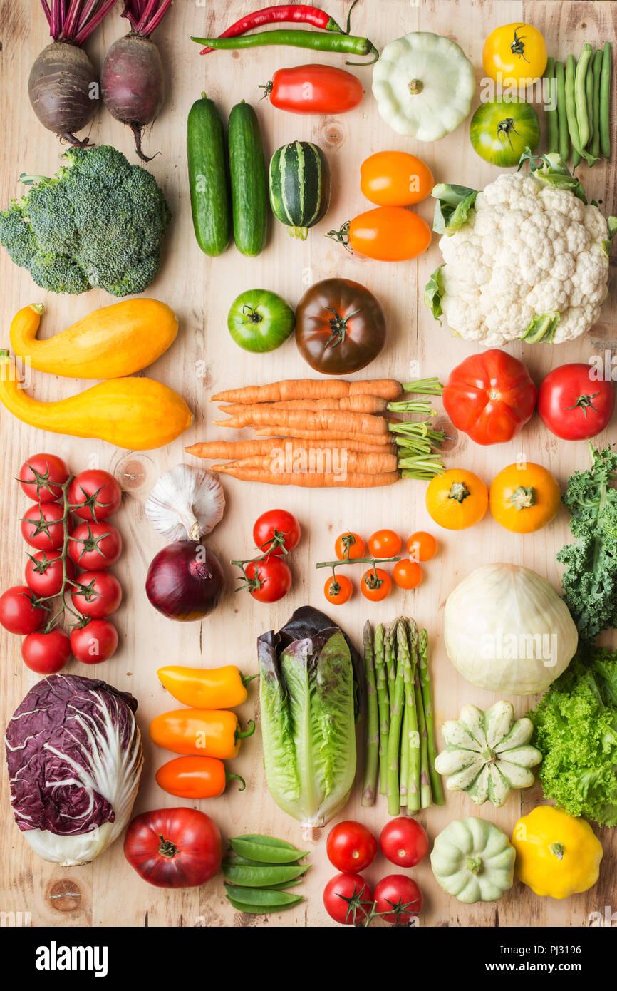 Assortimento di coloratissimi fresche verdure organiche su legno tabella di pino, cucina creativa lo sfondo in una griglia, verticale, vista dall'alto, il fuoco selettivo Immagini Stock
