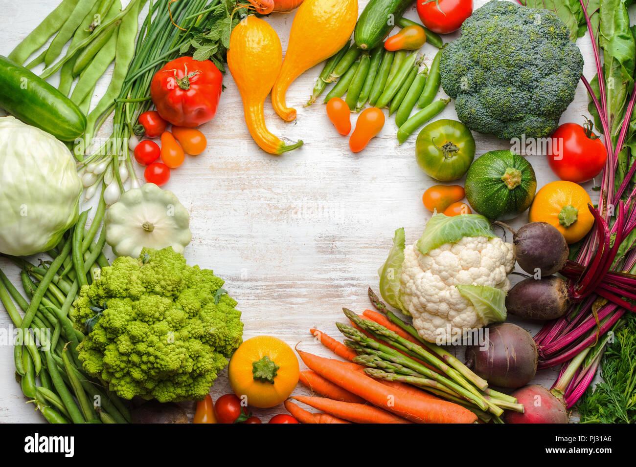 Prodotti freschi di fattoria, colorato cornice fatta di verdura biologica e le erbe sul bianco sullo sfondo di legno, sfondo sani, copiare lo spazio per testo, vista dall'alto, il fuoco selettivo Immagini Stock