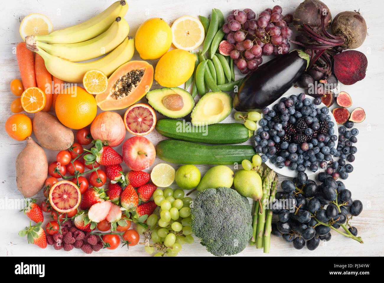 Mangiare sano concetto, assortimento di rainbow frutta e ortaggi, frutti di bosco, banane, arance, uve, broccoli, barbabietole rosse sul bianco tavola disposta in un rettangolo, vista dall'alto, il fuoco selettivo Immagini Stock