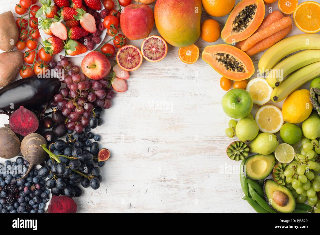 Mangiare sano, frutta e vegetablesrainbow su off tavolo bianco, copiare lo spazio per testo, vista dall'alto, il fuoco selettivo Immagini Stock
