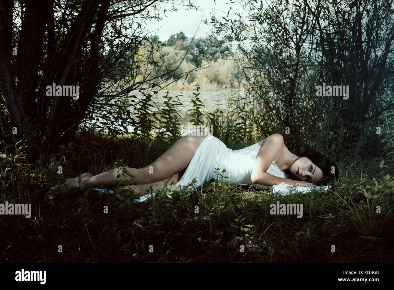 Pallida donna in abito bianco giacente sul terreno, scena da favola Immagini Stock