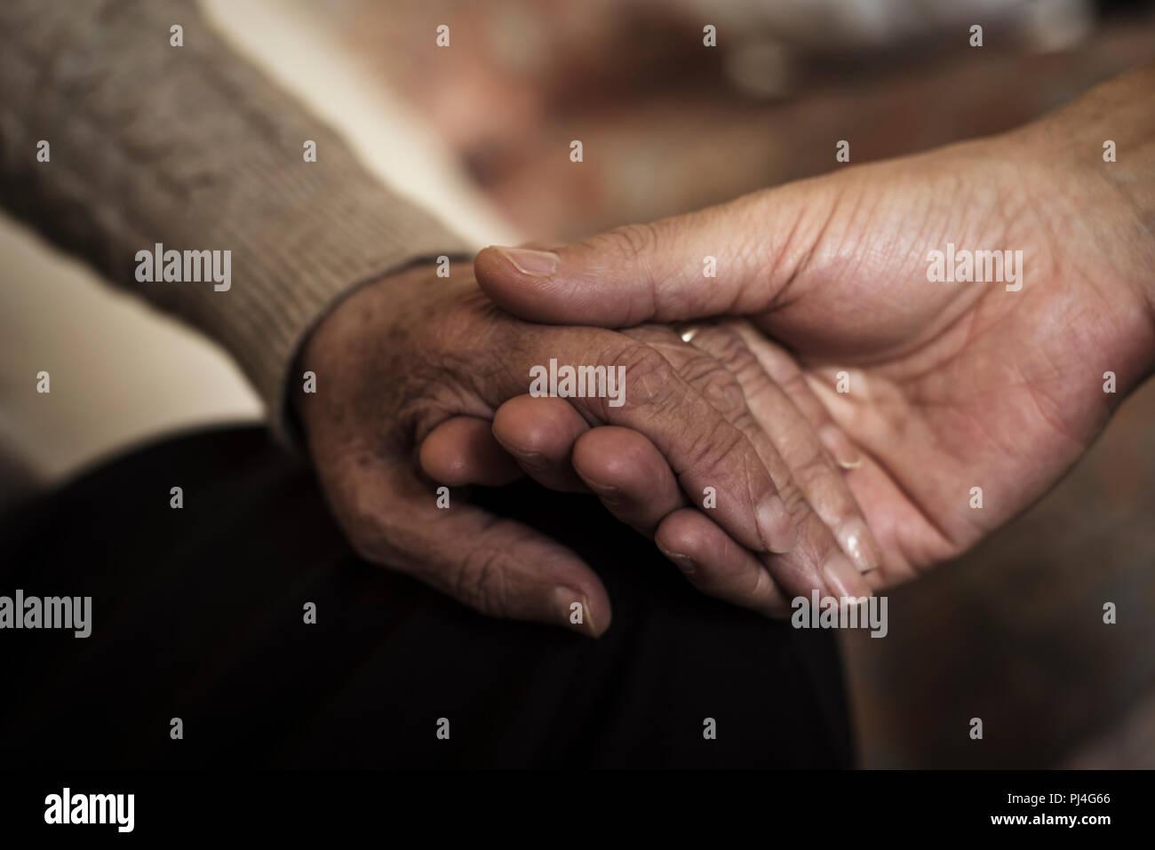 Primo piano di un giovane uomo caucasico tenendo per mano di una vecchia donna caucasica con affetto Foto Stock