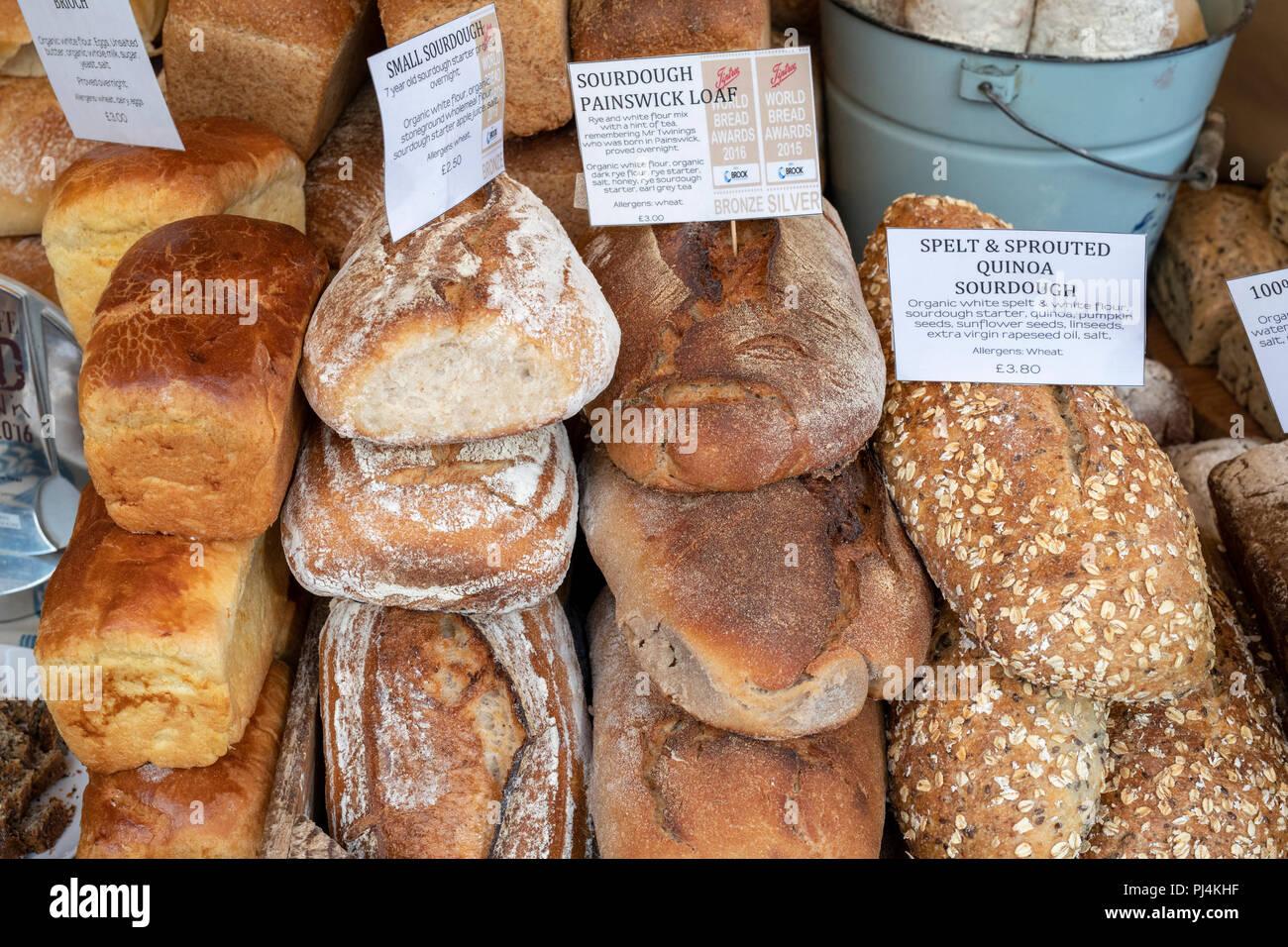 Pane di pasta acida per la vendita su l'artigiano panettiere stallo a stroud farmers market. Stroud, Gloucestershire, Inghilterra Immagini Stock