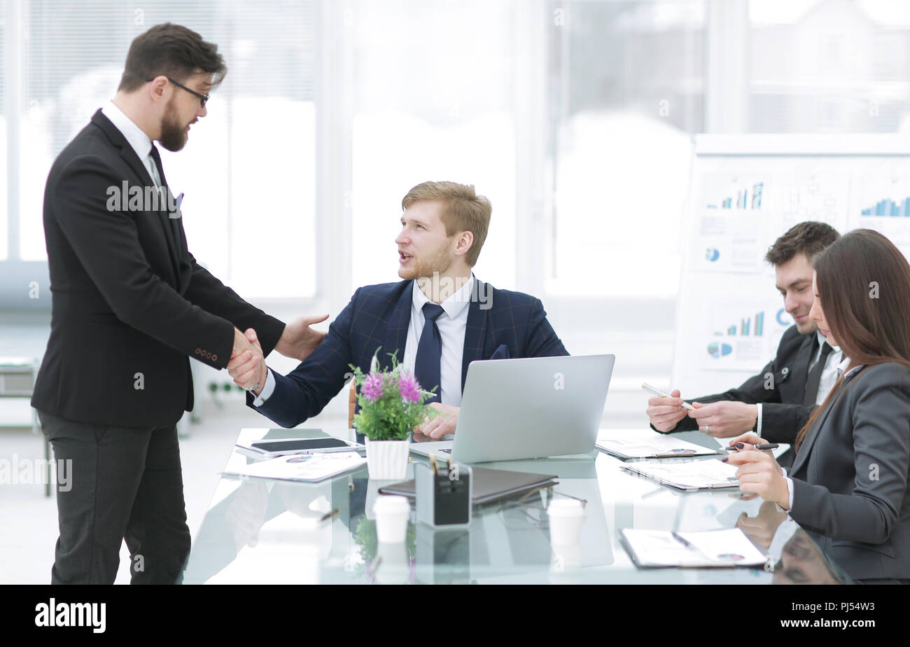 Stretta di mano il Manager e il dipendente nel posto di lavoro Immagini Stock