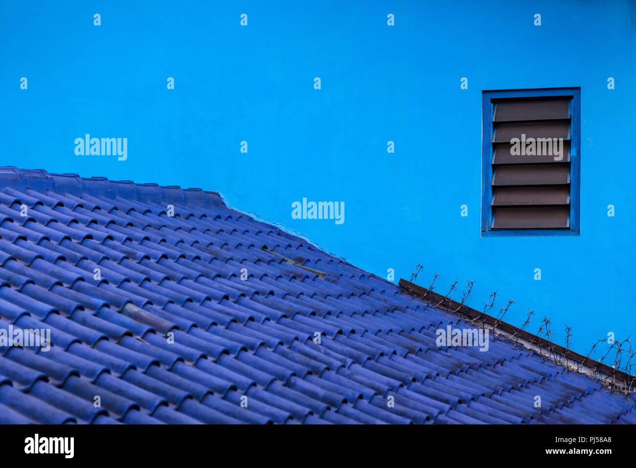 Sfondo blu. Muro di casa, tetto di tegole dipinte in varie sfumature di colore blu. Villaggio Kampung Biru è un luogo popolare per visitare per tour della città a piedi. Foto Stock
