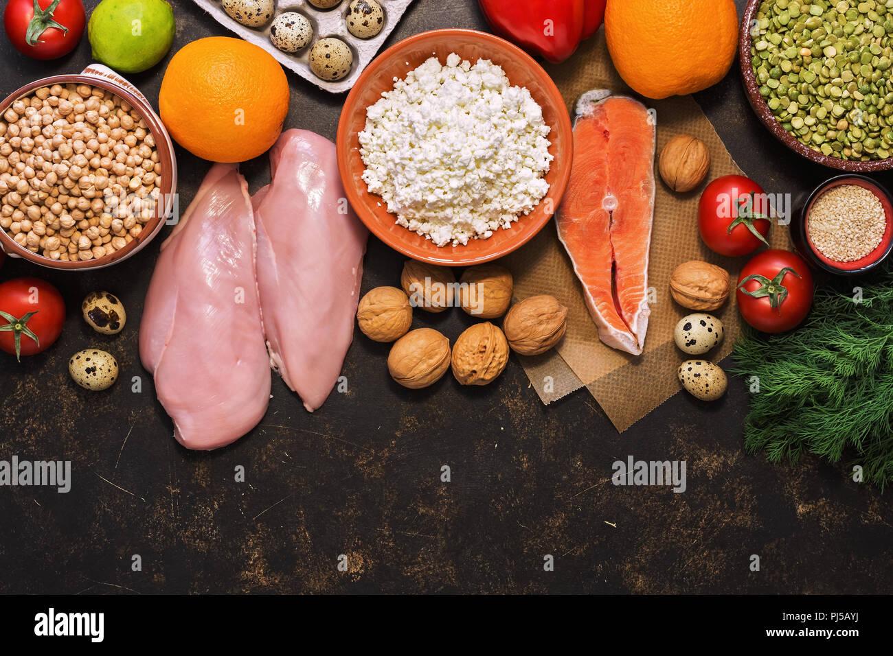 Cibo sano su uno sfondo scuro, salmone, filetto di pollo, frutta, verdura, cereali, formaggio. Vista superiore, lo spazio per il testo. Il concetto di mangiare sano. Immagini Stock