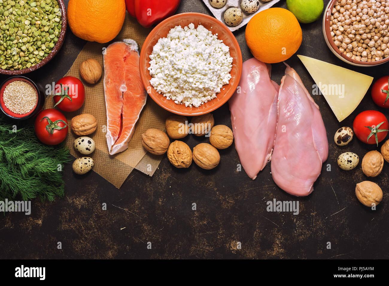 Sfondo con cibo sano. Pesce rosso, filetto di pollo e verdure, frutta, cereali, latticini, uova di quaglia. Vista superiore, copia dello spazio. Immagini Stock
