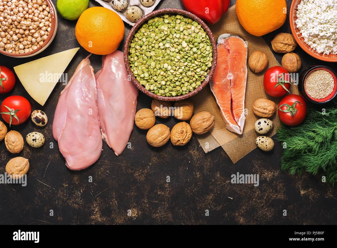 Un assortimento di cibi sani su uno sfondo scuro. Ortaggi, frutta, pesce, pollo, latticini, uova, i dadi. Vista superiore, lo spazio per il tuo testo. Lay piatto Immagini Stock