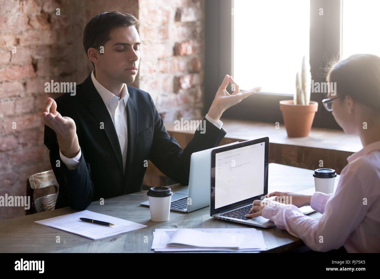 La meditazione al lavoro nella parte anteriore del computer portatile Immagini Stock