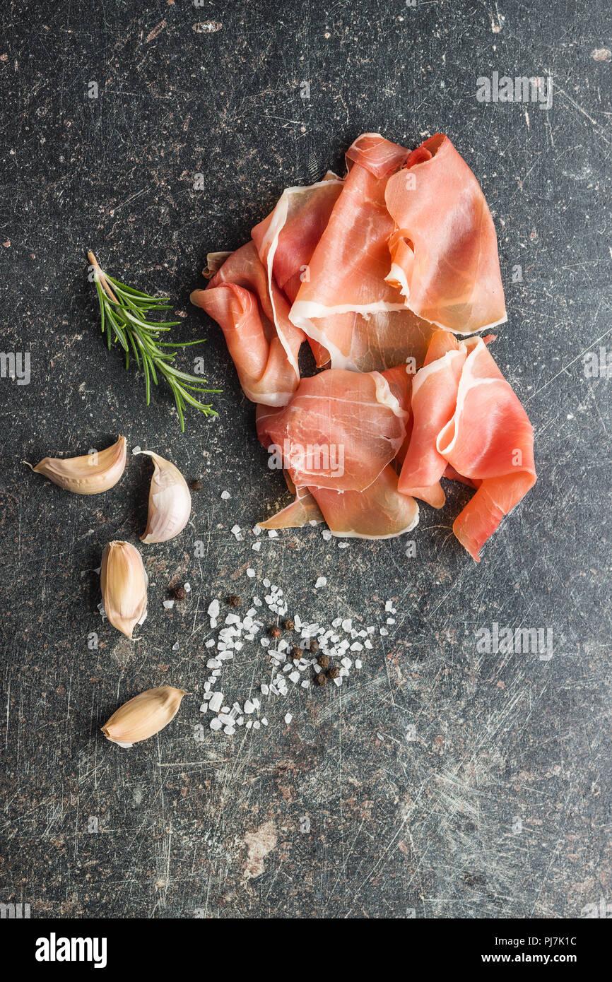 Italian prosciutto crudo o jamon con rosmarino, aglio, pepe e sale. Immagini Stock