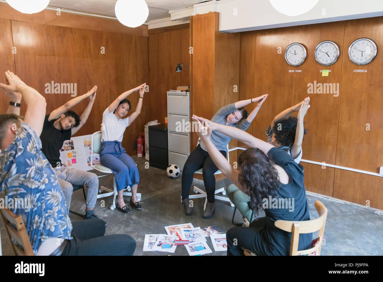 Azienda creativa persone stretching, prendendo una pausa in riunione Immagini Stock