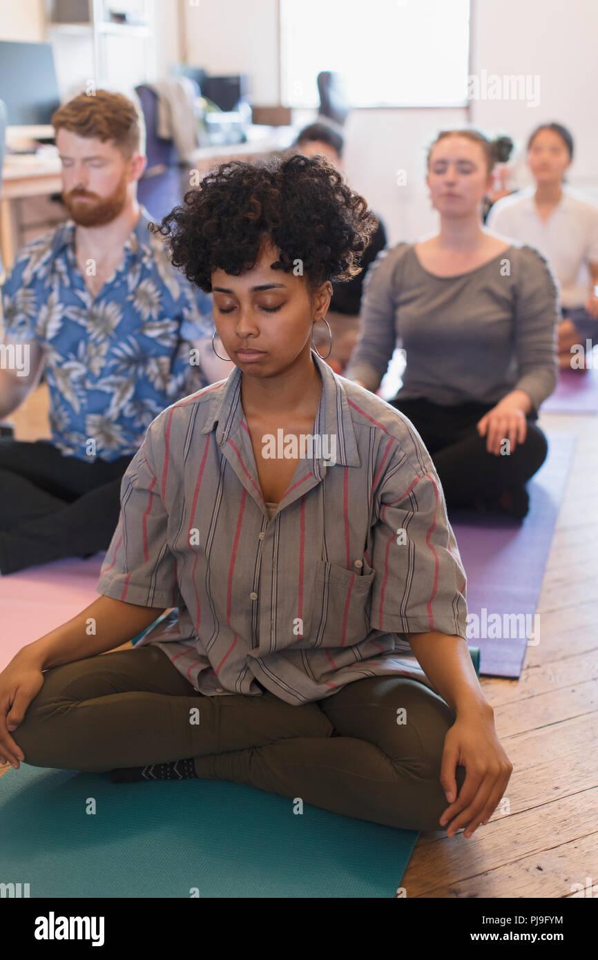 Serena azienda creativa persone meditando in ufficio Immagini Stock
