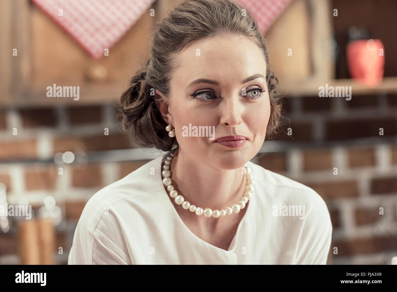 Close-up verticale di sorridere donna adulta in eleganti abiti vintage e collana di perle che guarda lontano Immagini Stock