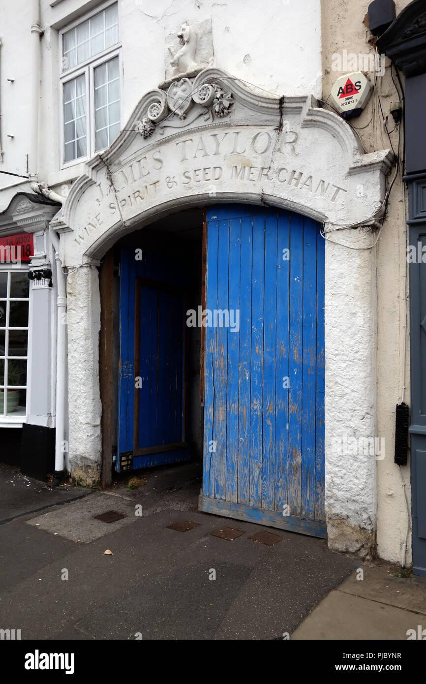 """Arco in pietra sopra la porta al vecchio cortile è inscritto con un tardo XIX secolo C aggiunta, """"James Taylor acquavite di vino & negoziante di sementi"""" Immagini Stock"""