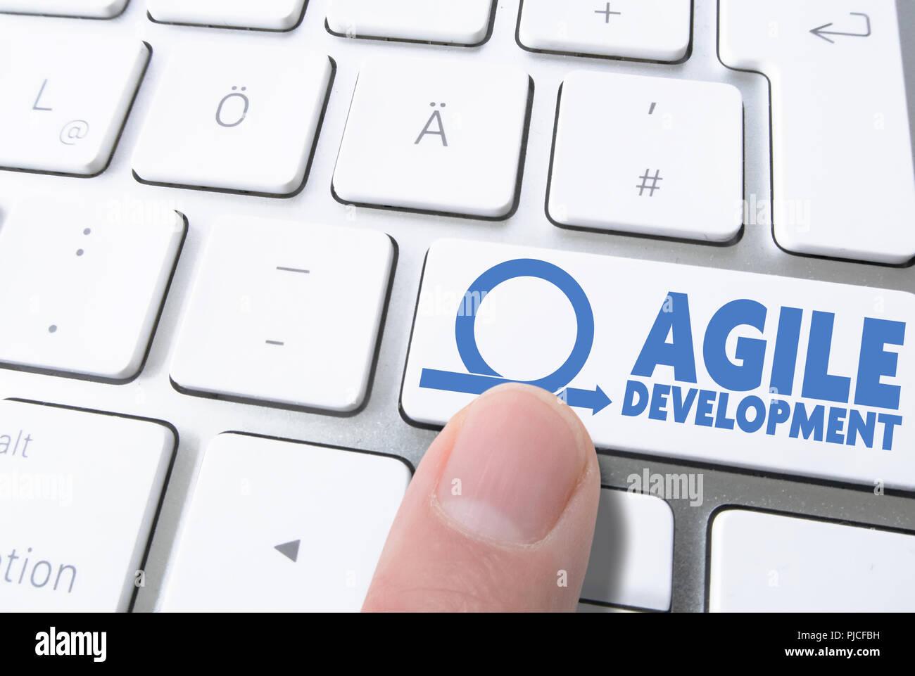 Dito premendo il tasto marcato sviluppo agile sulla tastiera del computer Immagini Stock