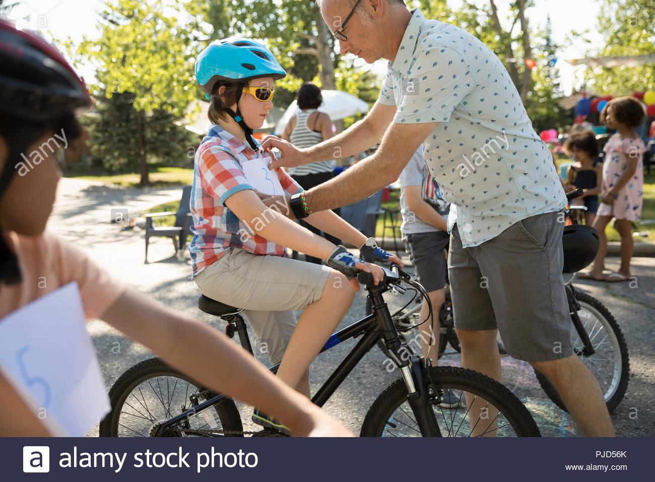 Padre maratona di pinning bib su sun la preparazione per la gara di moto ad estate quartiere block party Immagini Stock
