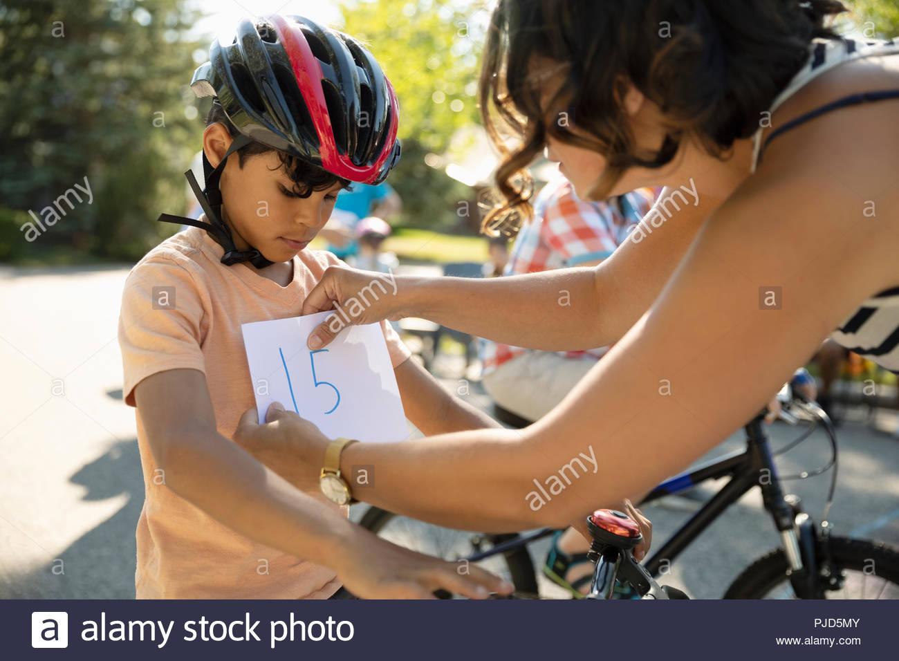 Madre maratona di pinning bib sul figlio la preparazione per la gara di moto Immagini Stock