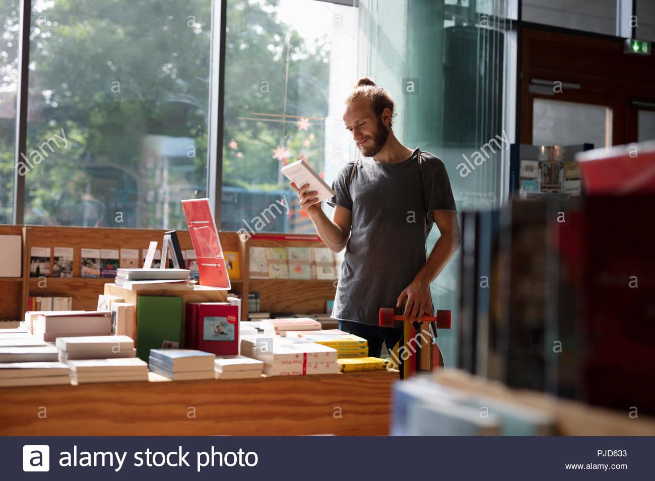 Uomo con negozi di skateboard in bookstore Immagini Stock