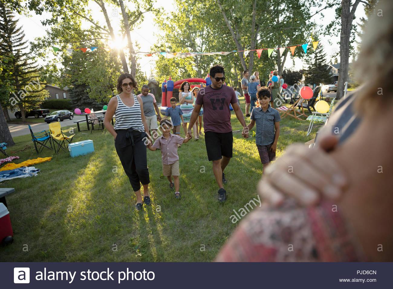 Famiglia Holding Hands, passeggiate in estate quartiere block party in posizione di parcheggio Immagini Stock