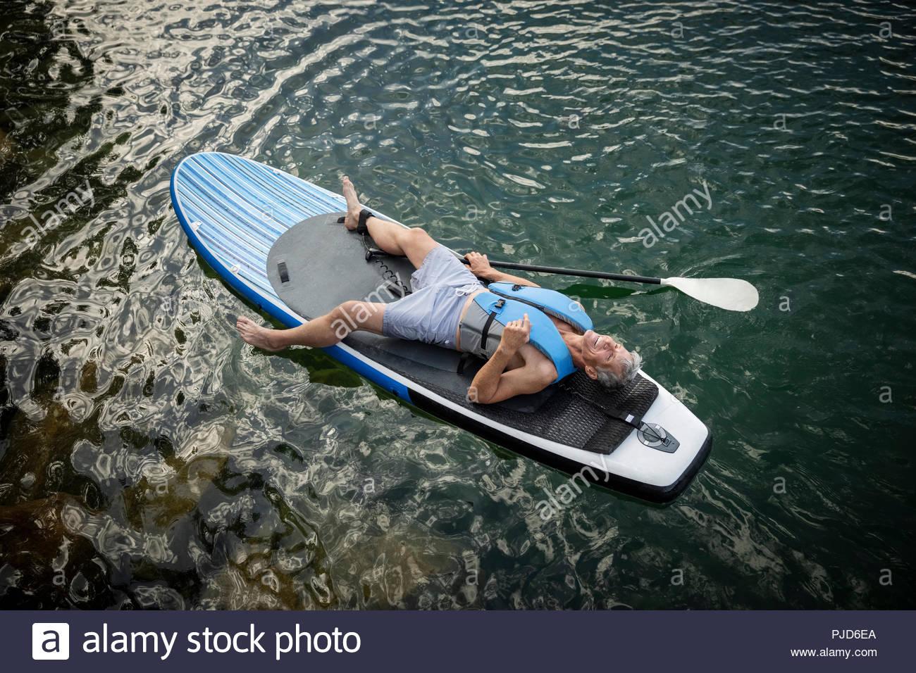 Serena uomo maturo rilassante, posa su paddleboard sul lago Immagini Stock