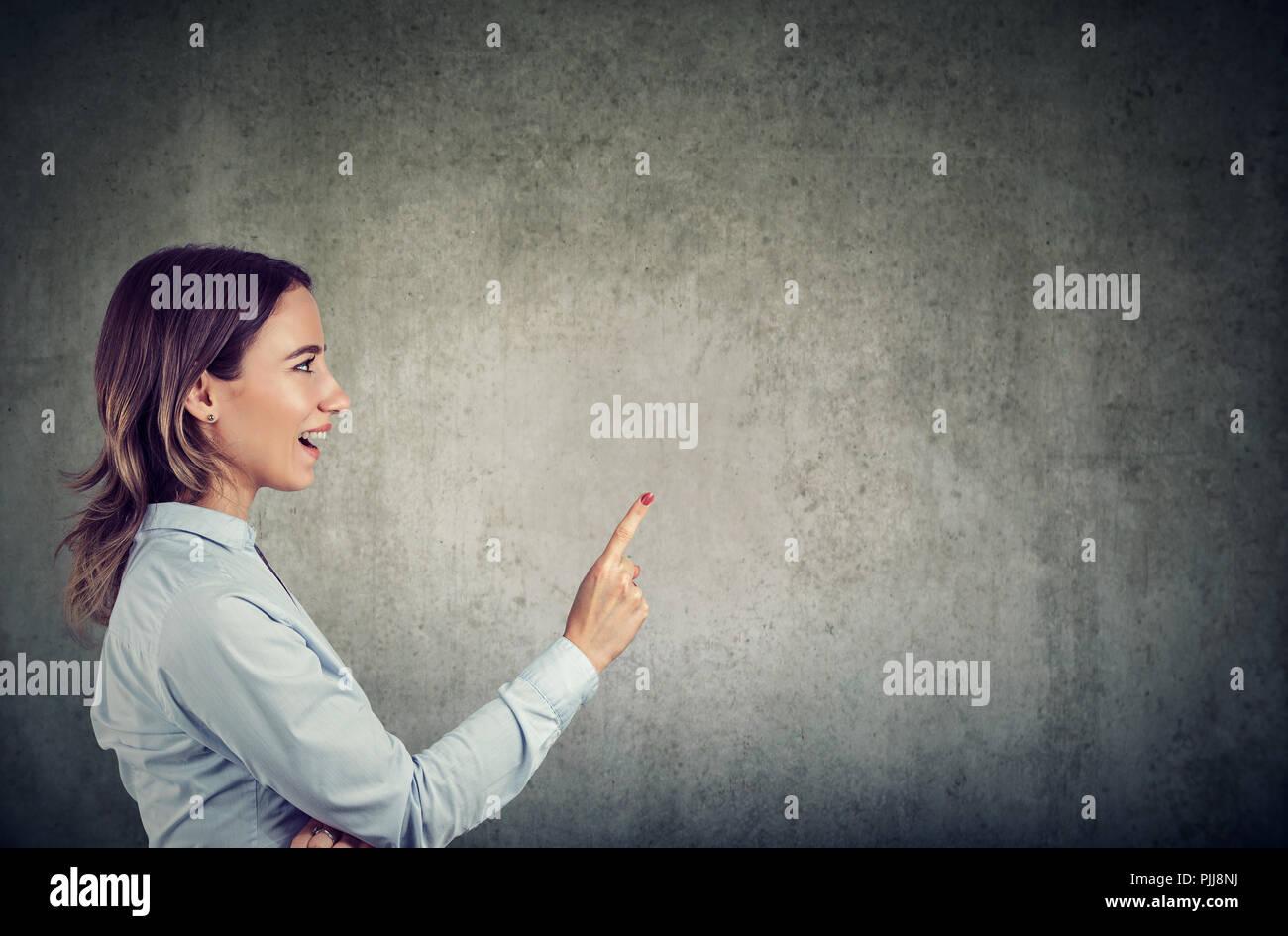 Vista laterale di Excited donna tenendo un dito avente brillante idea su sfondo grigio Immagini Stock