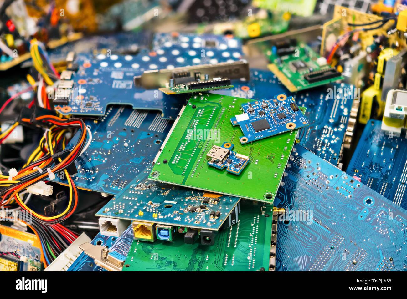 E-cumulo di rifiuti. Scartato parti di un computer portatile. I connettori per circuito stampato, le schede del notebook. Colorato sfondo sfocato. Componenti del PC. Per lo smaltimento dei rifiuti elettronici, industria. Immagini Stock