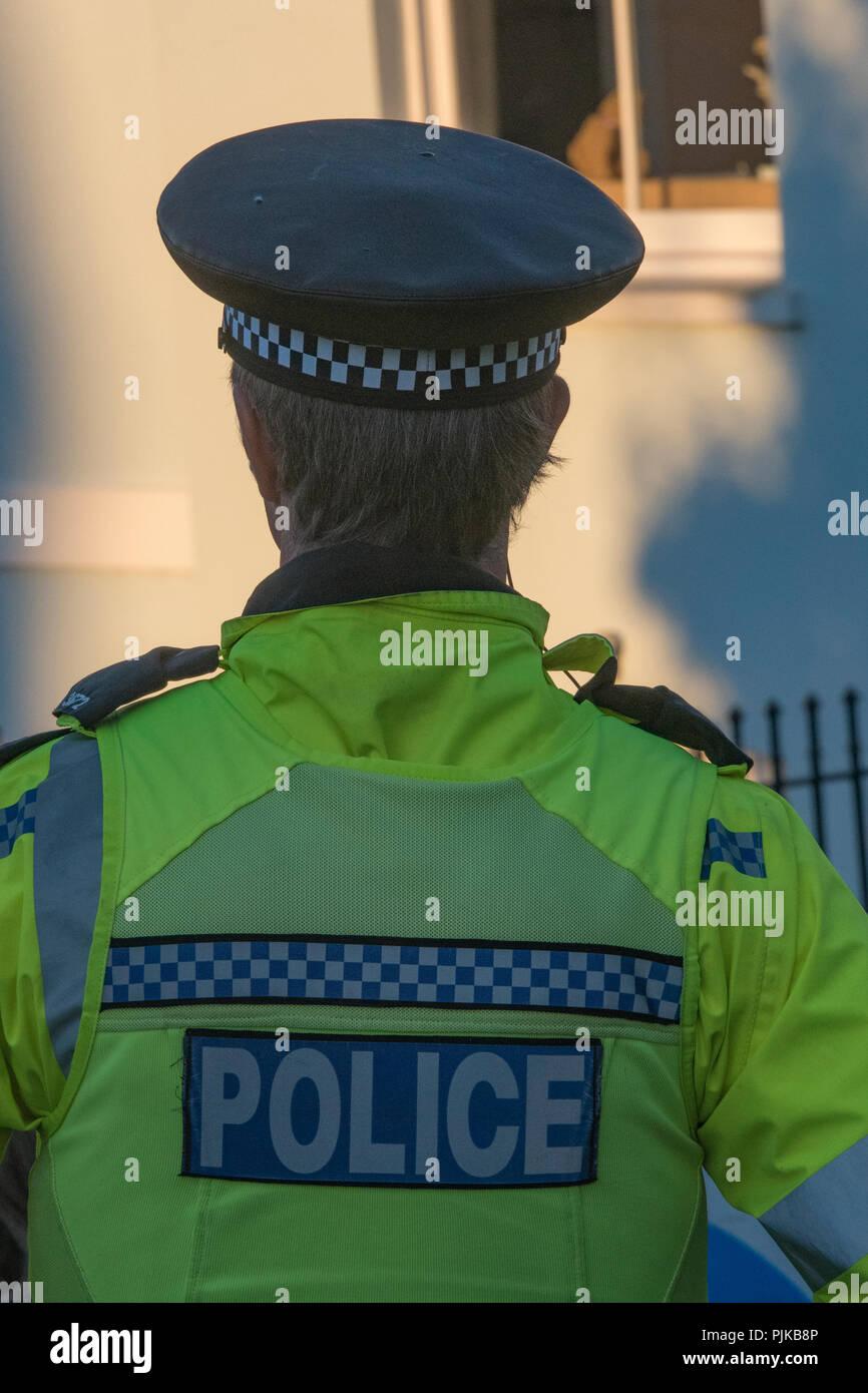 Ufficio di polizia in occasione di un evento mantenendo la pace che indossa un luminoso giallo ad alta visibilità camicia e polizia berretto. Immagini Stock