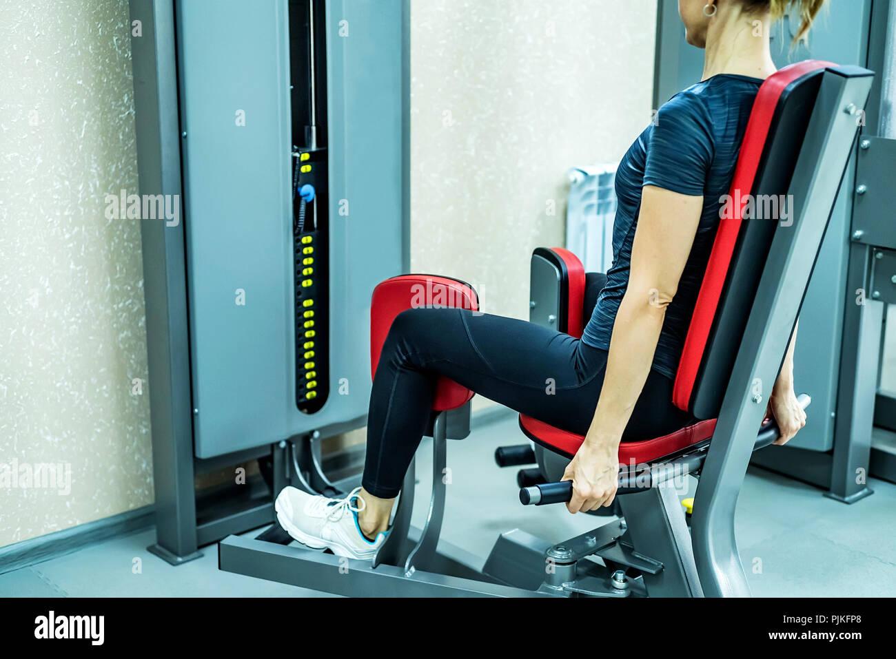 Vista laterale giovane donna gamba fa esercizi in palestra Immagini Stock