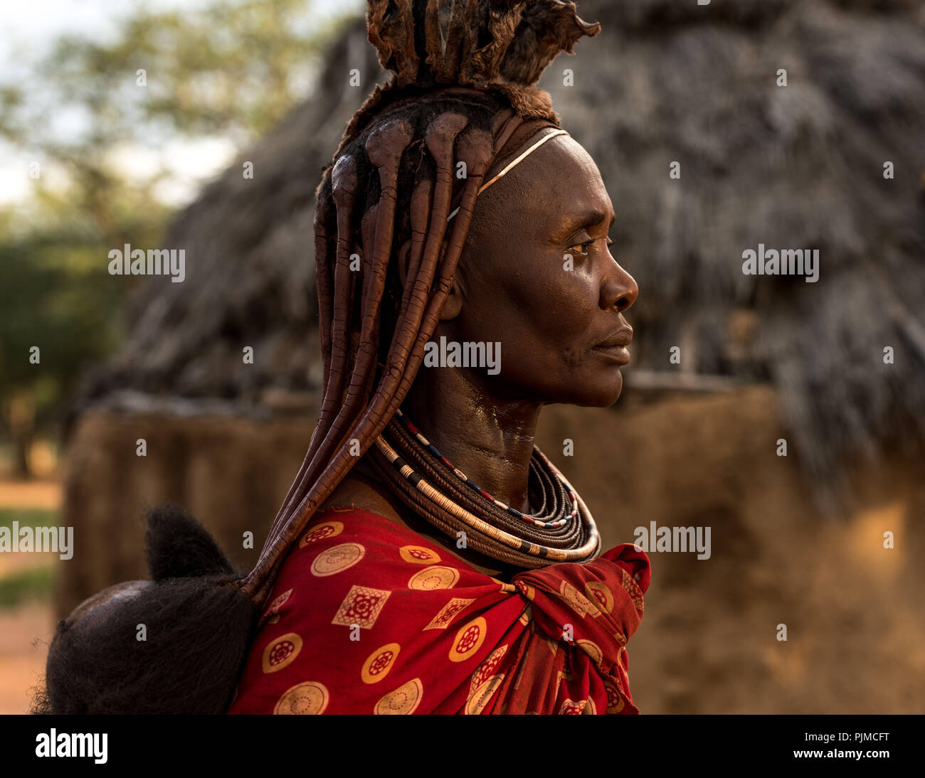 Ritratto di una donna Himba nell'ultima luce del sole, profilo laterale. Il bambino sulla schiena è solo visibile Immagini Stock