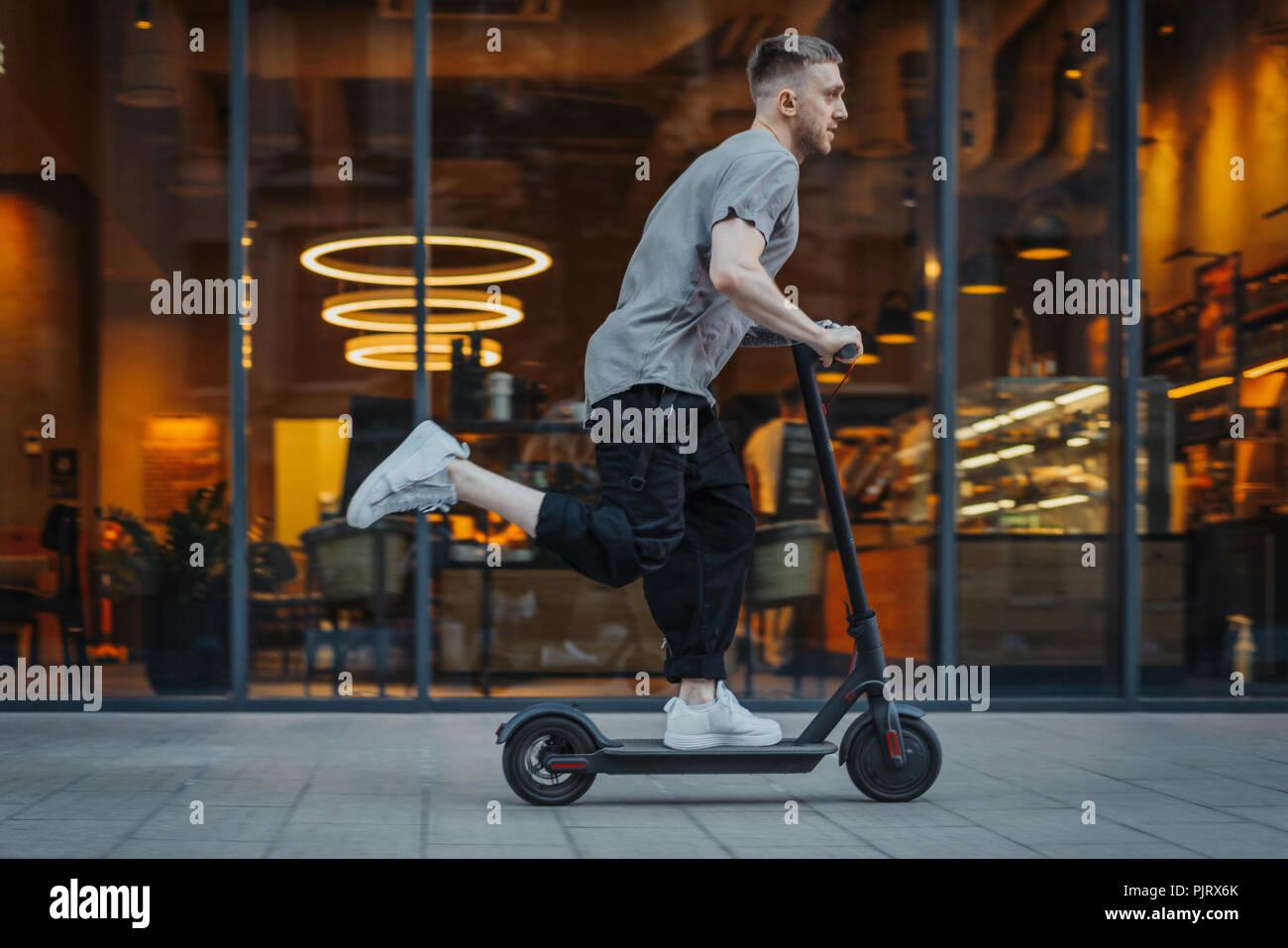 Attraente uomo a cavallo di un kick scooter a cityscape sfondo. Immagini Stock