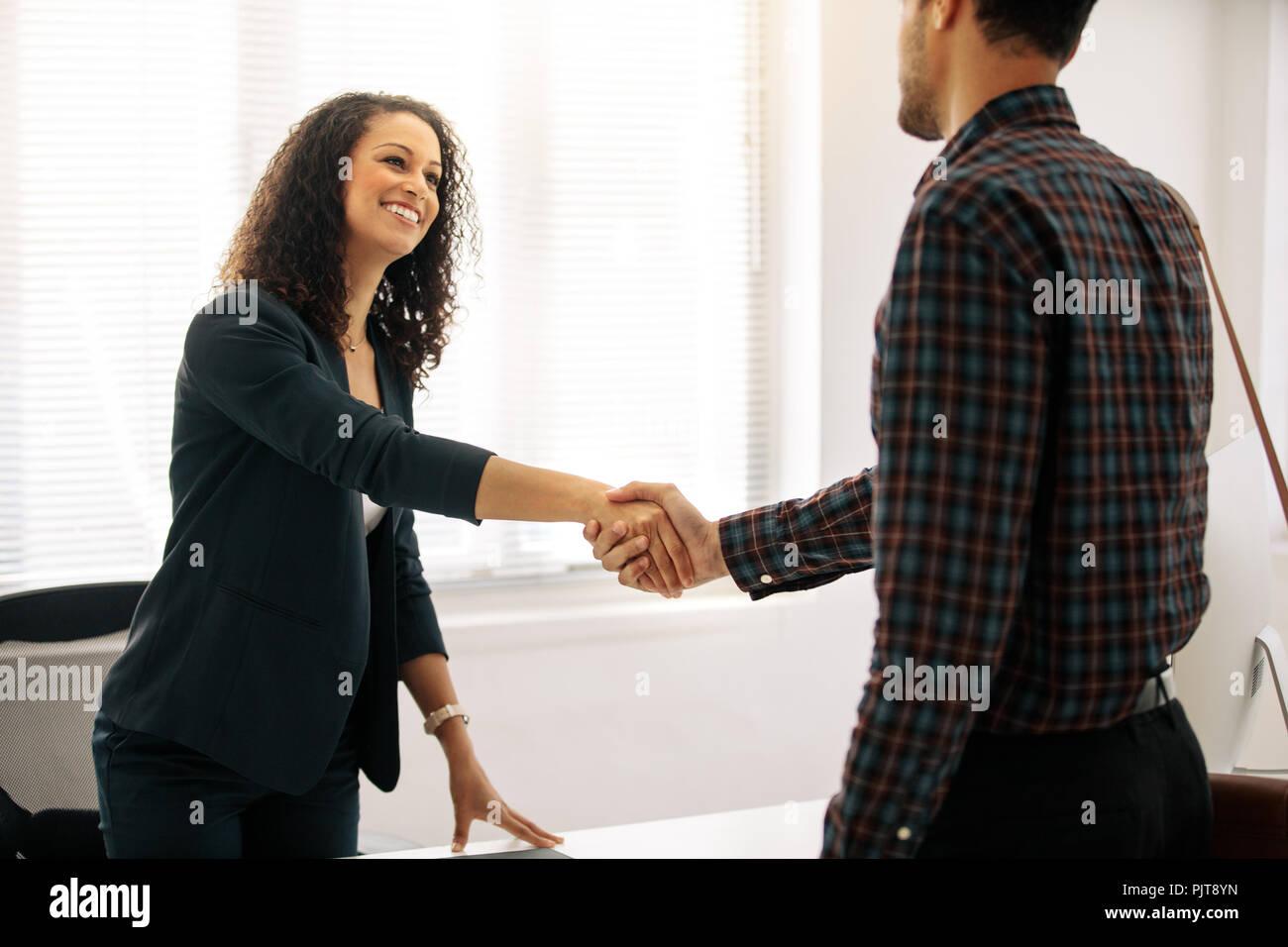 Business Partner riunione in ufficio agitando la mano. Imprenditrice donna in abiti formali saluto un imprenditore alla sua tavola in ufficio. Immagini Stock