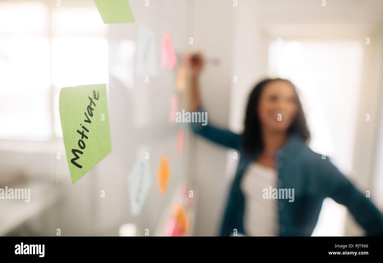Immagine di sfocatura di un imprenditrice incollando sticky notes sulla parete di vetro con la messa a fuoco su un post-it motivare scritto su di esso. Immagini Stock