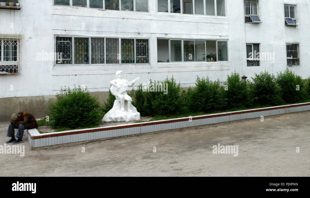 Il contrasto di una stanche e affaticate cercando lavoratore seduto da statua bianca di un felice chitarrista, Kaesong, Corea del Nord Immagini Stock