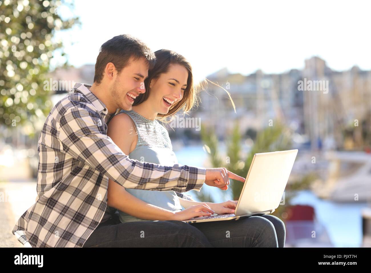 Coppia felice utilizza un laptop seduto in una porta su vacanze estive Immagini Stock