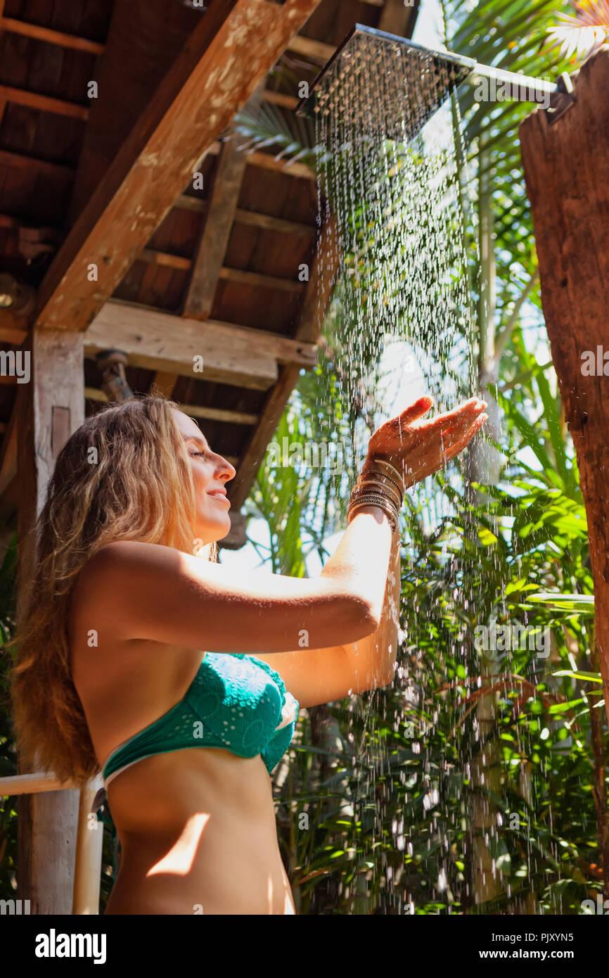 Bella ragazza prende la doccia. Donna stanno sotto la caduta di gocce di acqua in bagno esterno sulla veranda aperta con vista giardino nella villa di lusso Immagini Stock