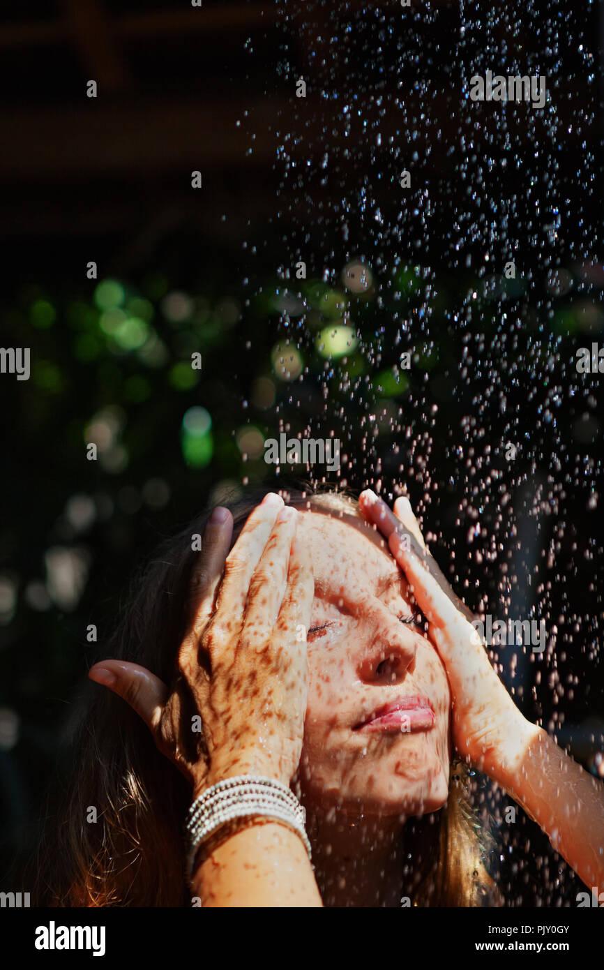 Bella ragazza prendere doccia donna stanno sotto la caduta di gocce di acqua in bagno esterno sulla veranda aperta con splendida vista sul giardino di villa di lusso Immagini Stock