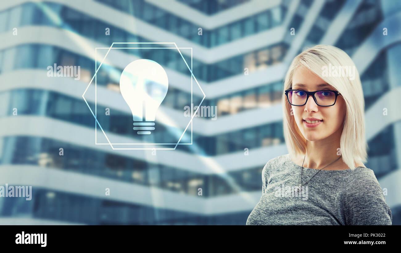 Bella donna che indossa occhiali guardando telecamera avente idea come icona lampadina glow sulla schermata digitale interfaccia. Creatività intelligen artificiale Immagini Stock