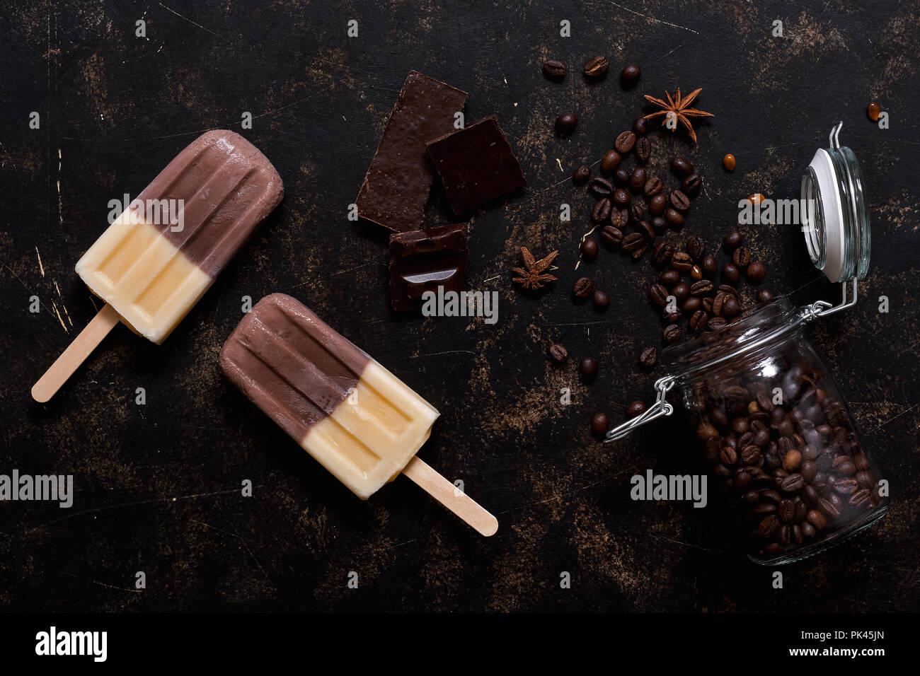 Doppio gelati su un bastone marrone-beige. Gelato caffè su uno sfondo scuro, vista dall'alto. Immagini Stock