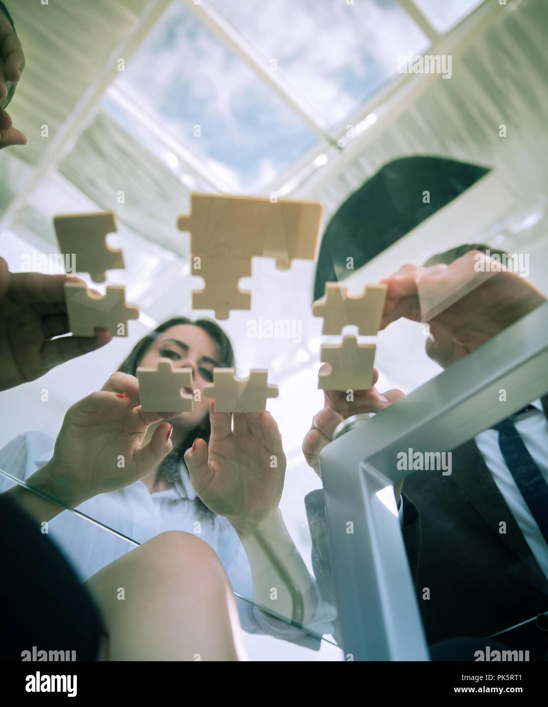 Vista inferiore. team aziendale di piegatura di pezzi di puzzle. . Immagini Stock