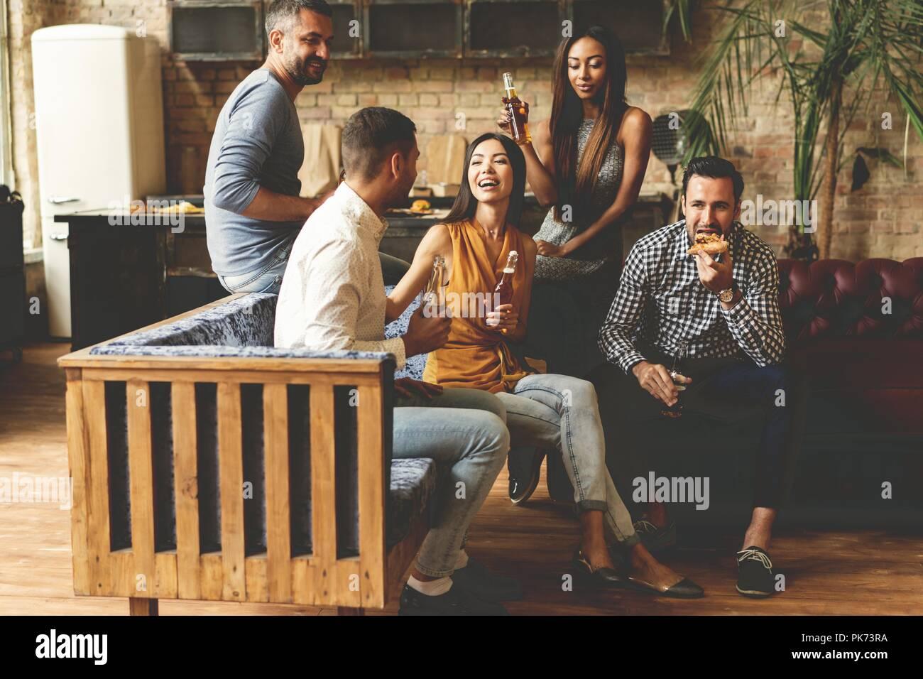 Trascorrere molto tempo con i migliori amici. Il gruppo di allegro giovani gustando cibi e bevande mentre trascorrere del tempo piacevole nel confortevole sedie sulla cucina insieme. Immagini Stock