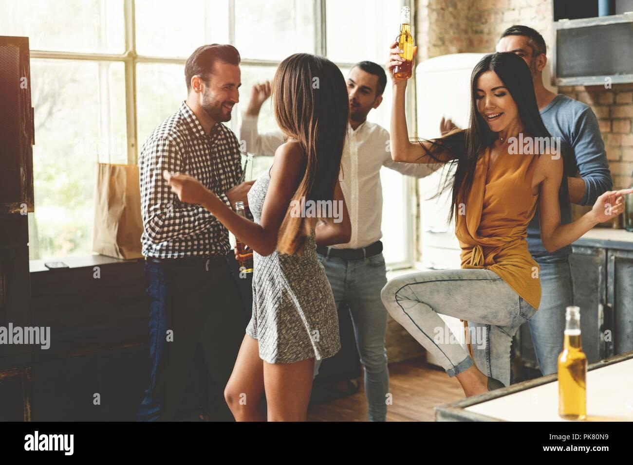 Godendo di partito con i migliori amici. I giovani allegri ballare e bere mentre godendo home partito sulla cucina. Immagini Stock