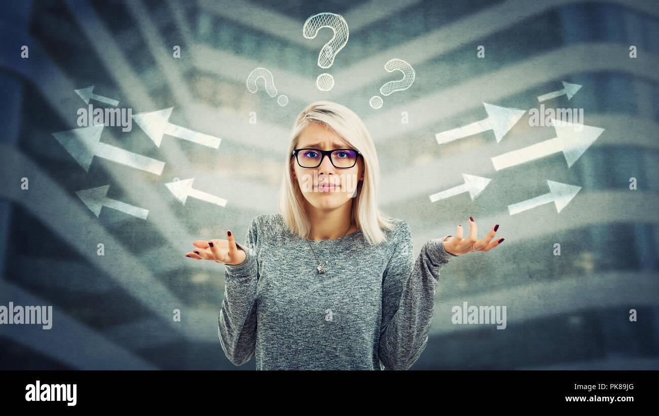 Confuso giovane donna con gli occhiali e frustrato gesto a mano hanno di scegliere nella direzione della freccia, a sinistra o a destra con i contrassegni di interrogazione al di sopra di hea Immagini Stock