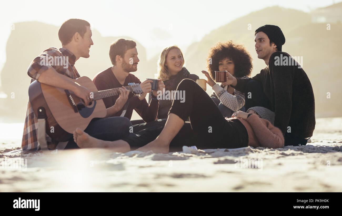 Giovane uomo a suonare la chitarra per gli amici sulla spiaggia. Gruppo di amici aventi parti in riva al mare. Foto Stock