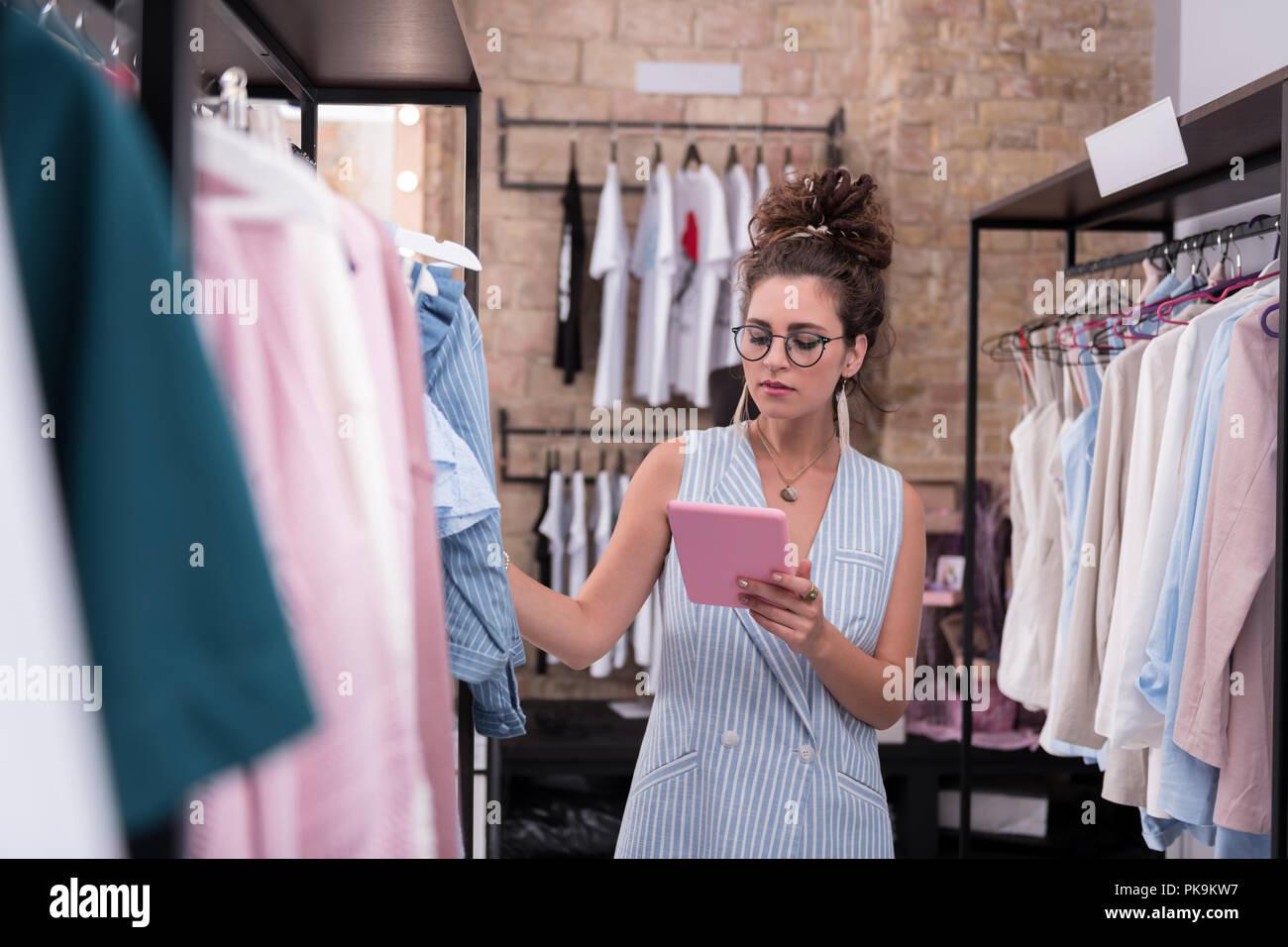 Femmina pensieroso shop assistant verifica le dimensioni disponibili Immagini Stock
