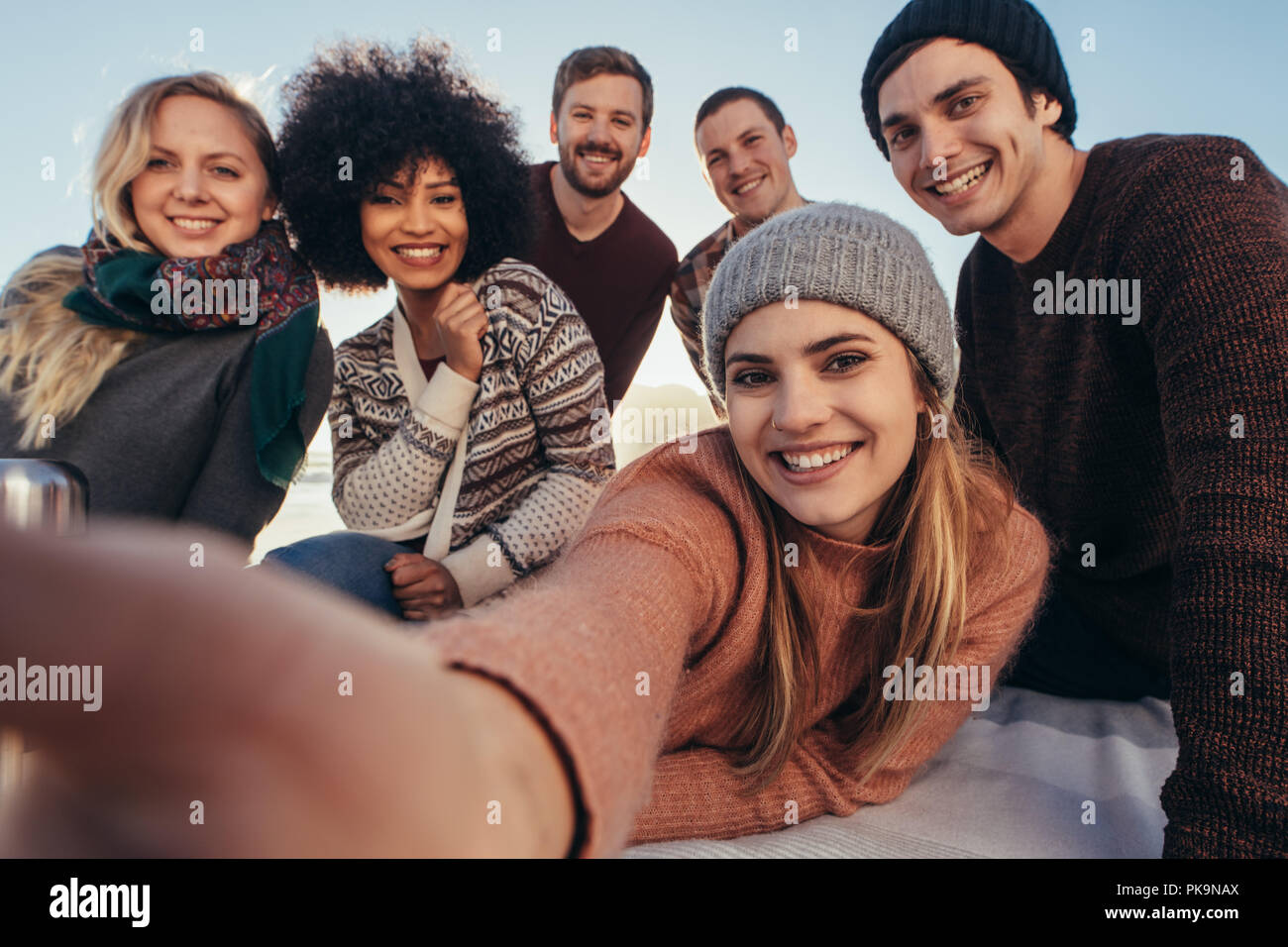 Giovani amici prendendo selfie durante le feste in spiaggia. Gruppo di razza mista amici prendendo selfie sulla riva del mare. Immagini Stock