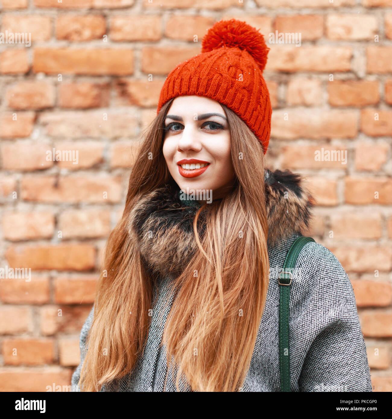4badbdafc59e Bella ragazza sorridente vicino a Brick Parete rossa in giornata invernale