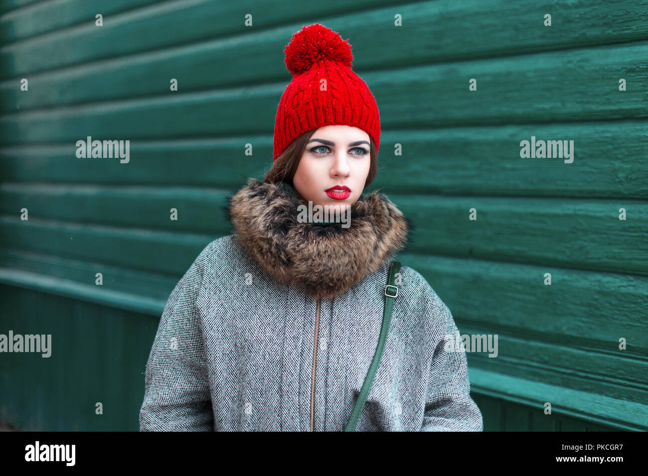 2f693e625d79 Elegante giovane ragazza russa nel quartiere alla moda di abbigliamento  invernale in piedi vicino a un verde parete in legno