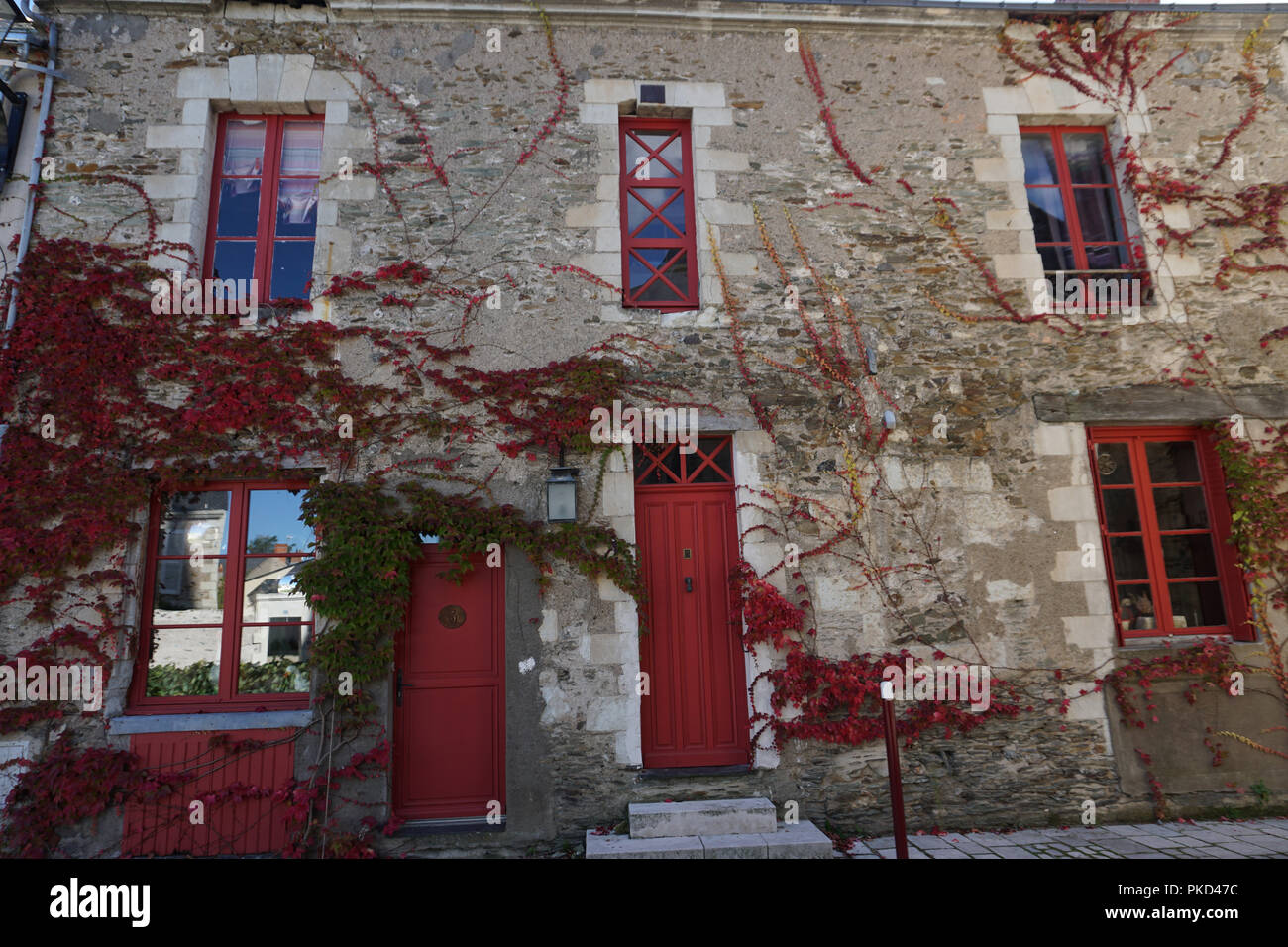 Facciata Casa Di Campagna rosso e verde edera crescente selvatici su una vecchia